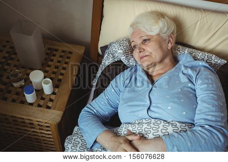 Worried senior woman relaxing on bed and pill boxes kept on a side table in bedroom