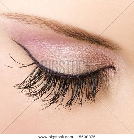 Woman eye with pastel color makeup and long eyelashes