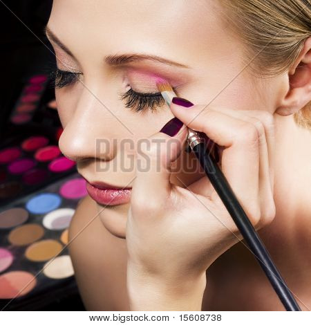 Makeup artist applying pink eyeshadow