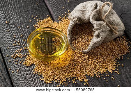 Grain mustard in a linen bag and mustard oil in a glass bowl. It is used in dietary and healthy nutrition cosmetics herbal medicine. The source of vitamins and polyunsaturated fatty acids