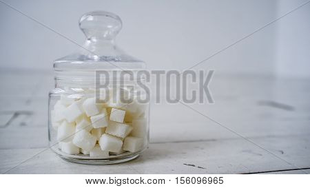 White sugar lumps in a glass jar on the wooden table painted in white color close-up