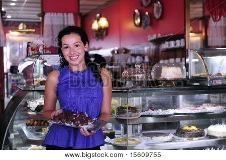 owner of a small business store showing her tasty cakes