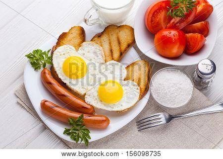 Breakfast on Valentine's Day - fried eggs in the shape of a heart and sausages, milk, tomatoes on the white wooden table.