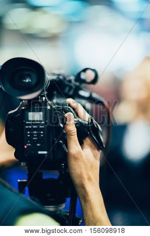 Television camera recording a publicity event, toned image