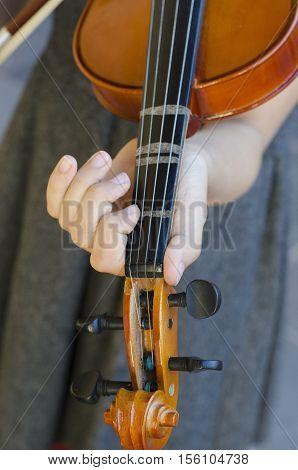 Teenage girl with violin on gray dress