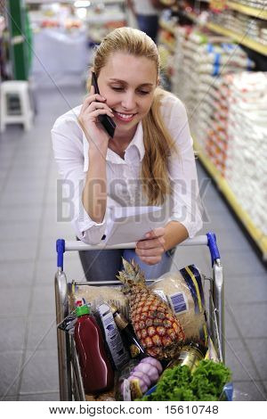 Blond woman in the supermarket  talking on phone with shopping list