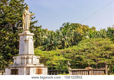 Statue of Jesus in Se Cathedral church around palm trees in Panaji Old Goa India