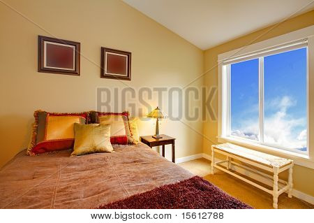 Brown Bed With Gold Pillows And Blue Window