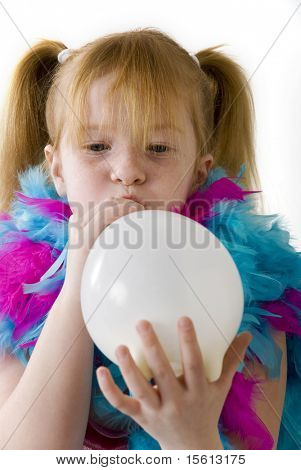 Red-haired girl is blowing a white balloon