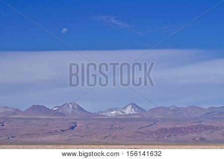Volcanoes landscape under a blue sky with visible moon.