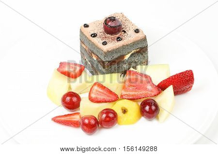 Black brownie chocolate cake pastry sliced fruit strawberry honeydew grapes kiwi