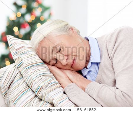 age, holidays, relax and people concept - happy senior woman sleeping on pillow at home over christmas tree background