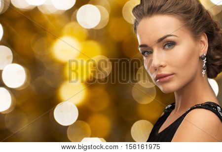 people, holidays, jewelry and luxury concept - woman in evening dress and earring over lights background