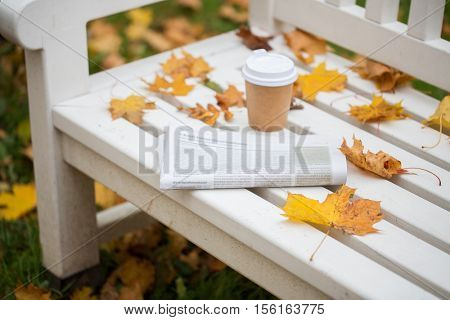 season and news concept - newspaper and coffee cup on bench in autumn park