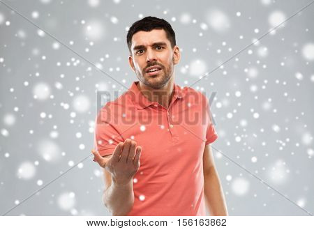emotion, gesture, winter, christmas and people concept - arguing angry man proving something over snow on gray background