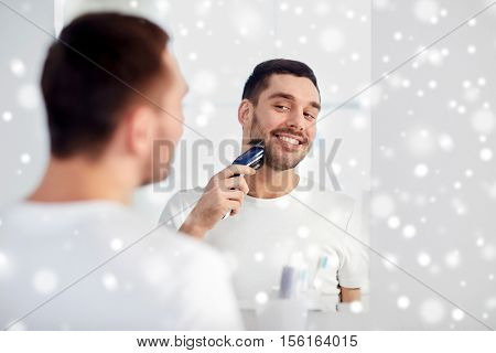 beauty, shaving, grooming and people concept - young man looking to mirror and shaving beard with trimmer or electric shaver at home bathroom over snow