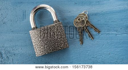 Padlock on a blue wooden background