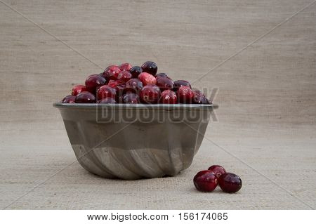 Close up of fresh red and maroon cranberries heaped in a  vintage ridged tin bowl or food mold with three berries outside the dish. Photographed against a ecru woven cloth background with fill flash and shallow depth of field.