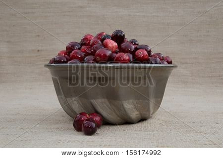 Close up of a fresh red and maroon cranberries heaped in a vintage ridged tin bowl or food mold with several berries outside of dish and  photographed against an ecru woven cloth background with shallow depth of field and fill flash.