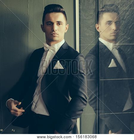 Man in suit gaped open with white bow tie handkerchief young elegant stylish turns sideway and reflects in mirror on grey background