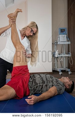 Physical therapist working with male patient. Streching patient's leg