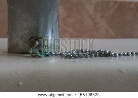 Calcium deposits on balls chain bathroom sink stopper brass oxide greenish color detail