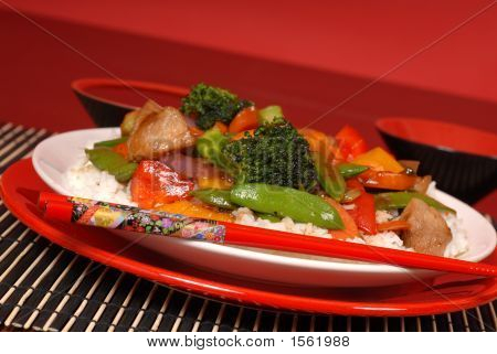 A Plate Of Stir Fry Pork With Chop Sticks