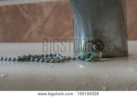 Calcium deposits on wet balls chain bathroom sink stopper brass oxide greenish color detail