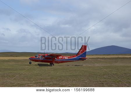 FALKLAND ISLANDS, OCTOBER 26, 2016: Small aircraft landing on a gravel airstrip on Saunders Island in the Falkland Islands