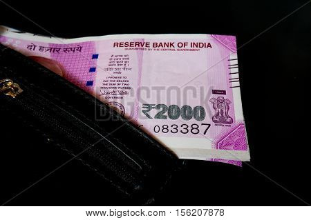 New Indian rupee 2000 note placed in a black leather wallet and isolated on black. The new currency has been introduced to curb black money