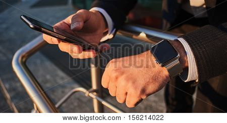 Hand with smart watch and a hand holding the cellphone