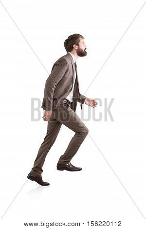 Side view of a bearded businessman climbing an invisible ladder. Concept of success and career growth. Isolated