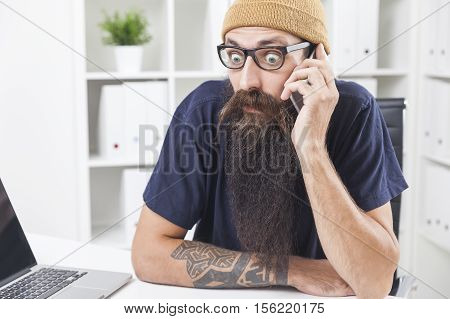 Baffled long bearded hipster is talking on the phone at his office. The laptop is standing on the desk