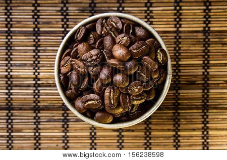 Coffee beans in cup with leaf symbol isolated on wooden background