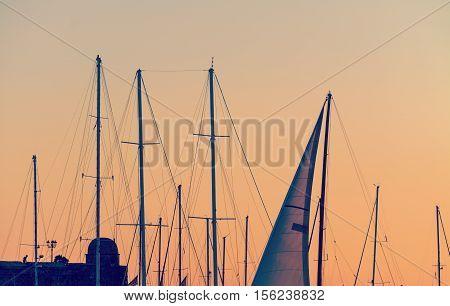 boat masts under an orange sunset. Shot in Alghero Sardinia