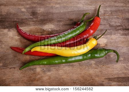 red and yellow chili pepers over wooden background