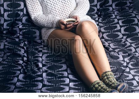 Detail of sexy young woman. Woman keep a coffee cup and sitting on a blanket.. Naked legs. Home atmosphere.