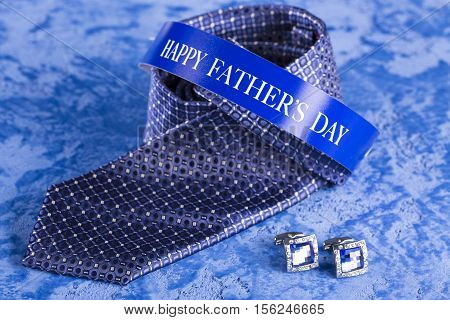 Blue tie and cufflinks on a blue marble background for the holiday Father's Day