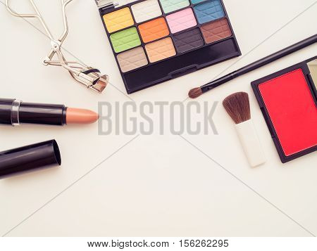 Top view of make up cosmetic products - eyeshadow lipstick eyelash curler brush on brush - vintage filter