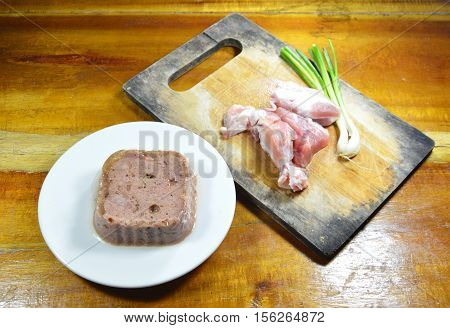 dog premium wet food and fresh raw pork on chop block
