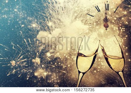 Glasses with champagne against fireworks and clock close to midnight - New Year, holiday background