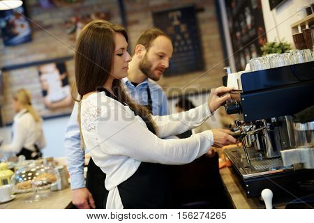 Waitress and waiter making coffee in cafeteria, using coffee machine.