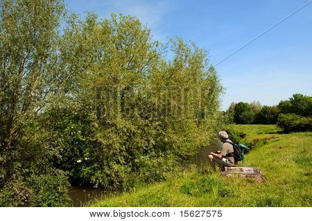 Man is resting near the river in nature landscape