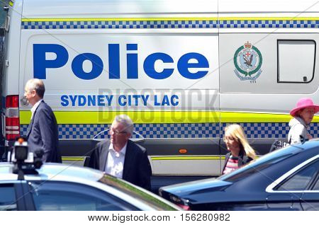SYDNEY - OCT 20 2016:People pass by Sydney Police vehicle.Australians believe the government need to prevent terrorist attack on home soil but concerns that Muslims being under increased surveillance