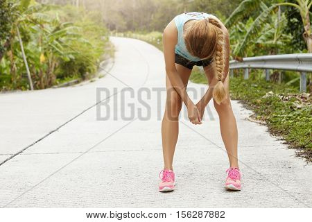 Tired Woman Runner Having Rest After Running Hard On Road In Forest, Bending Forward, Resting Elbows