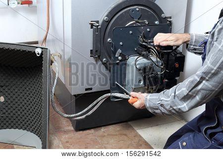 worker is repairing a heating burner in a house
