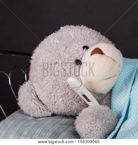 Sick concept. Teddy bear lying in bed with a temperature