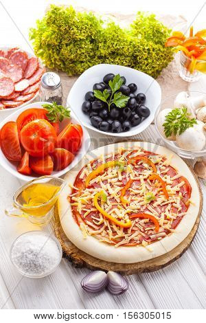Food ingredients for pizza on the white wooden table close up