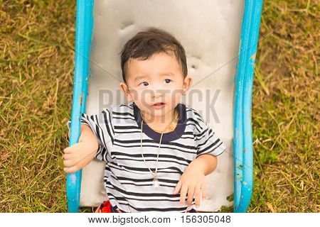 Little Asian kid playing and smiling at the playground under the sunlight in summer Kids play on school yard. Happy kid in kindergarten or preschool warm tone. shallow DOF