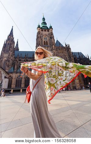 Female traveler with beautiful colorful handkerchief spinning on the background of the St. Vitus Cathedral, Prague, Czech Republic. Facade from the patio.